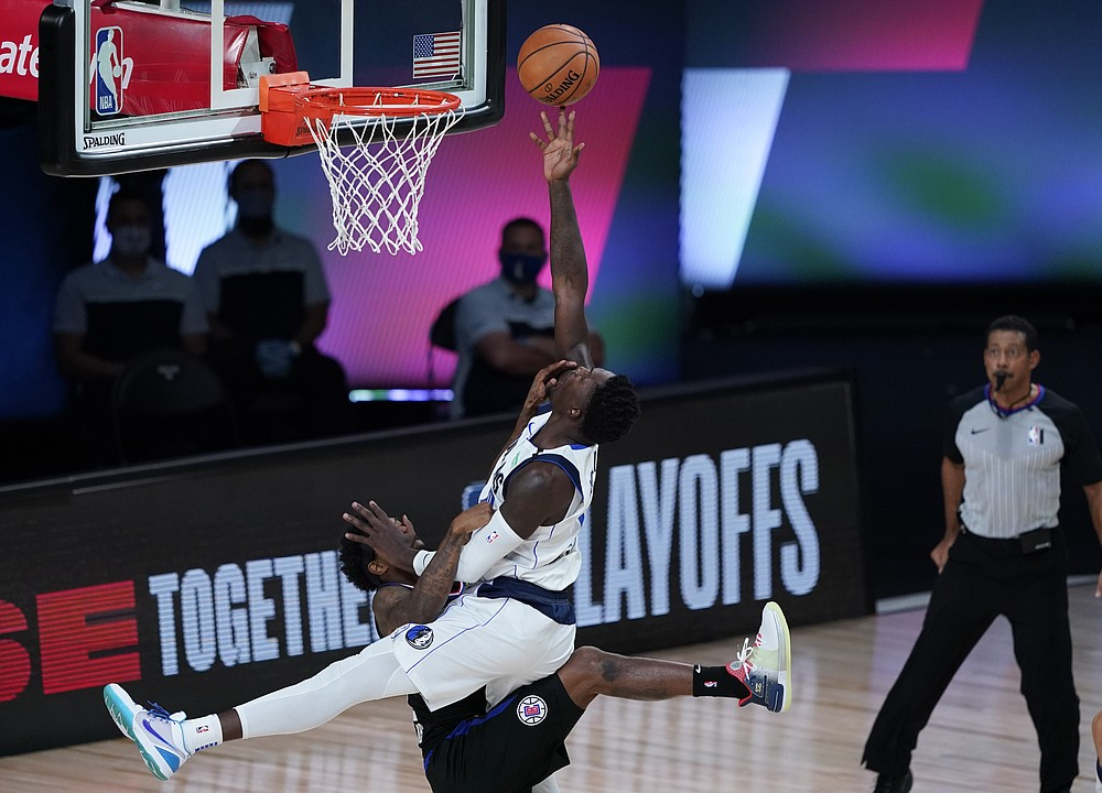 Los Angeles Clippers' Lou Williams (23) fouls Dallas Mavericks' Dorian Finney-Smith (10) during the first half of an NBA first round playoff game Sunday, Aug. 30, 2020, in Lake Buena Vista, Fla. (AP Photo/Ashley Landis)