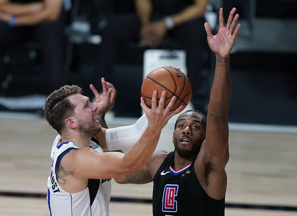 Los Angeles Clippers' Kawhi Leonard (2) fouls Dallas Mavericks' Luka Doncic (77) during the second half of an NBA first round playoff game Sunday, Aug. 30, 2020, in Lake Buena Vista, Fla. (AP Photo/Ashley Landis)