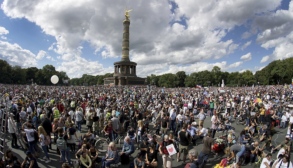 People gather at the Victory Column as they attend a protest rally in Berlin, Germany, Saturday, Aug. 29, 2020 against new coronavirus restrictions in Germany. Police in Berlin have requested thousands of reinforcements from other parts of Germany to cope with planned protests at the weekend by people opposed to coronavirus restrictions. (AP Photo/Michael Sohn)