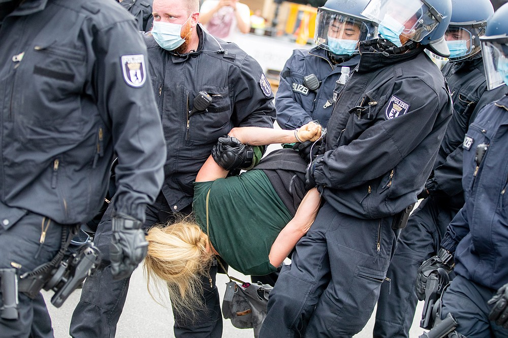 Police officers carry a woman at the Victory Column in a protest against the Corona measures in Berlin, Germany, Sunday, Aug. 30, 2020. (Christoph Soeder/dpa via AP)