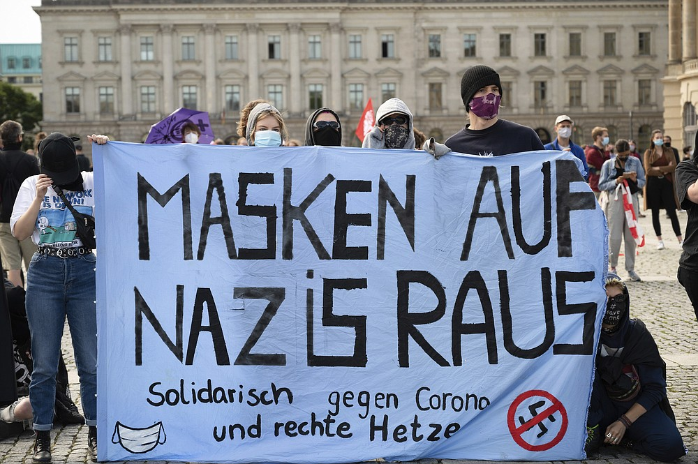 """Counter-demonstrators of a rally against the Corona measures gather and hold out a banner reading """"Masks on Nazis out"""" in Berlin, Germany, Saturday, Aug. 29, 2020. (Christophe Gateau/dpa via AP)"""