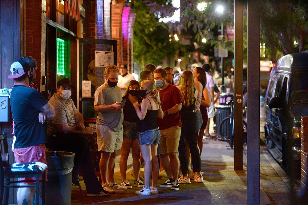 A line forms Friday, Aug. 28, 2020, outside a bar as staff monitors the number of people inside on Dickson Street in Fayetteville. Visit nwaonline.com/200906Daily/ for today's photo gallery. (NWA Democrat-Gazette/Andy Shupe)