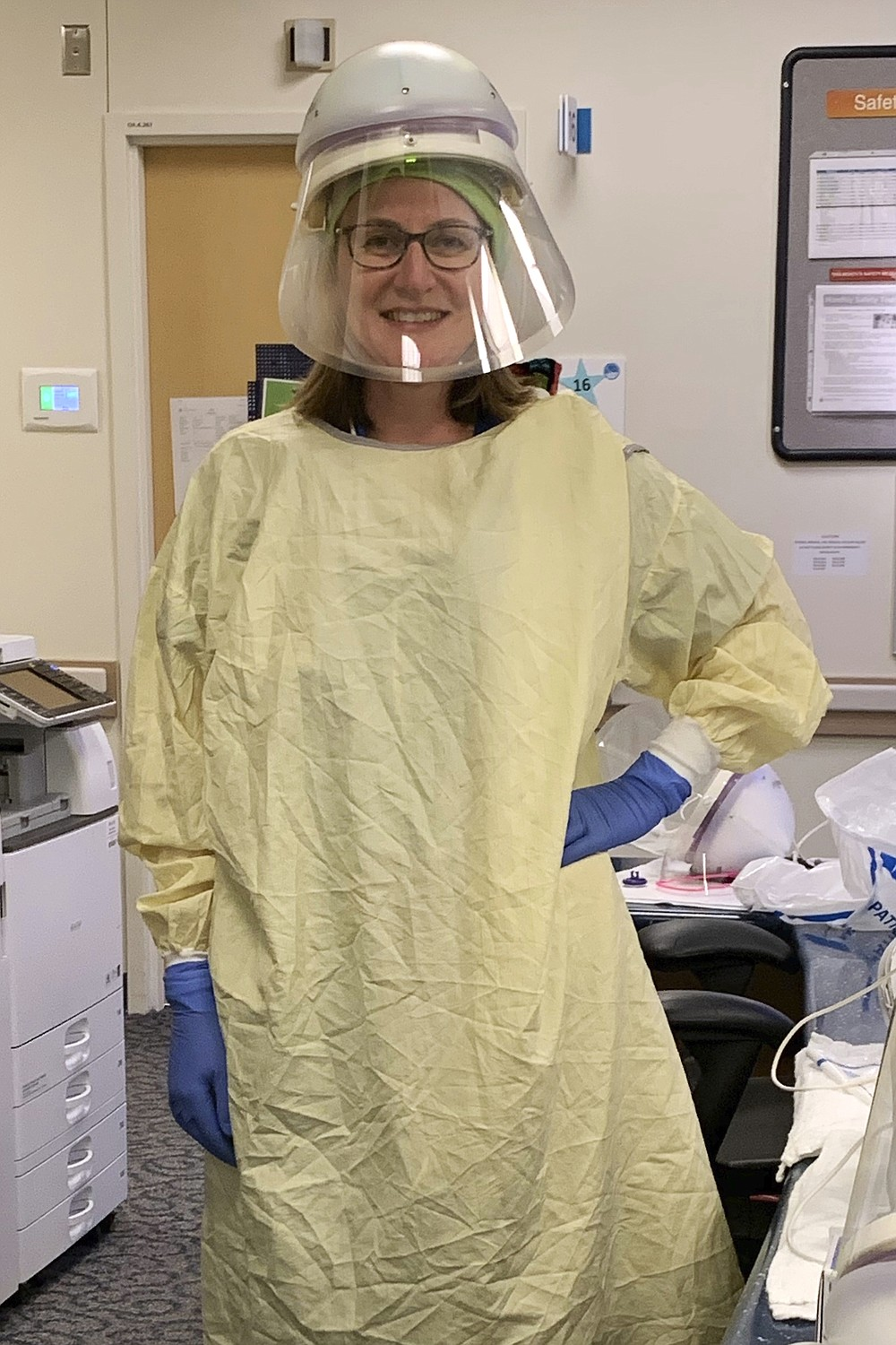 """In this undated photo provided by Cassie Docking, she poses at work as an urgent care nurse in Seattle. As the Summer of COVID draws to a close, many experts fear an even bleaker fall and suggest that American families should start planning for Thanksgiving by Zoom.   She is telling her parents — both cancer survivors — that Thanksgiving will be by FaceTime only. """"We all want to get to 2021 and if that's what it takes, that's what we'll do,"""" Docking said. (Courtesy of Cassie Docking via AP)"""