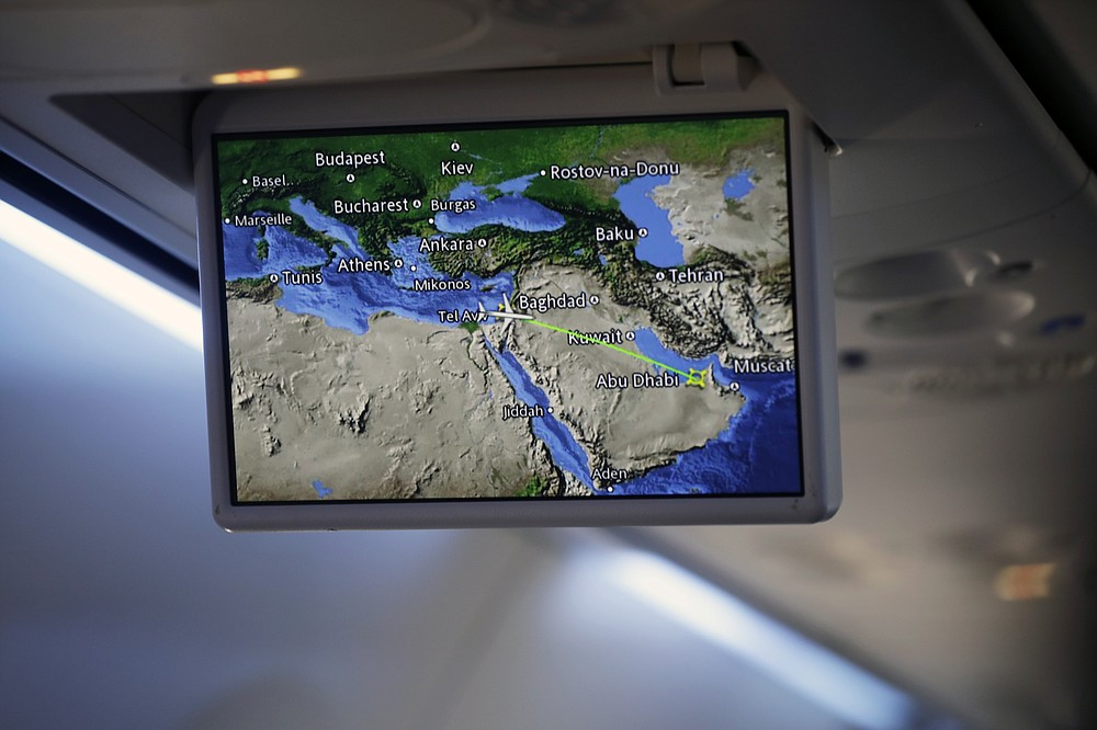 An overhead screen displays a map showing the flight route of an El Al plane from Israel en route to Abu Dhabi, United Arab Emirates, Monday, Aug. 31, 2020. The El Al plane carrying a high-ranking American and Israeli delegation to Abu Dhabi completed the first-ever direct commercial passenger flight to the UAE. The Israeli flag carrier's flight Monday marks the implementation of the historic U.S.-brokered deal to normalize relations between the Israel and the UAE. (Nir Elias/Pool Photo via AP)