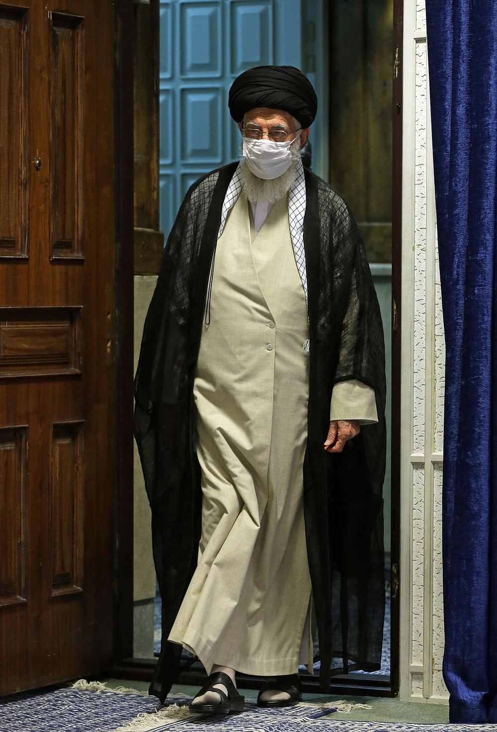 """In this picture released by the official website of the office of the Iranian supreme leader, Supreme Leader Ayatollah Ali Khamenei wearing a protective face mask to help prevent spread of the coronavirus arrives to attend a video conference with education ministry officials in Tehran, Iran, Tuesday, Sept. 1, 2020. Iran's supreme leader called the United Arab Emirates' recognition of Israel """"treason that will not last for long."""" (Office of the Iranian Supreme Leader via AP)"""