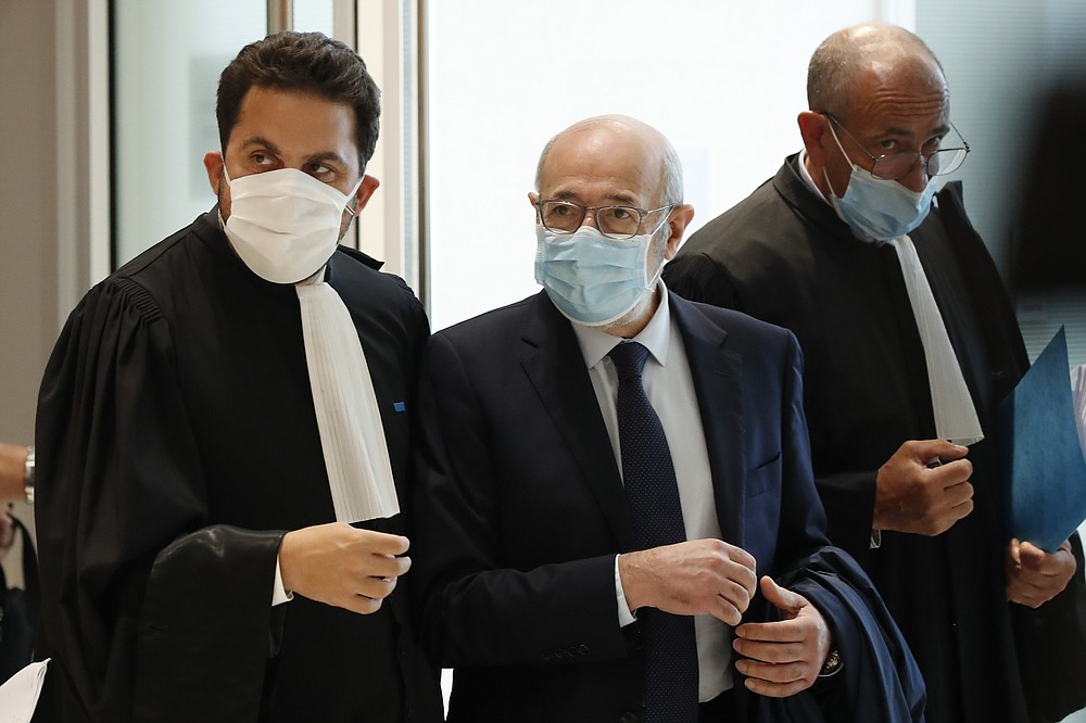 Chairman of the Representative Council of French Jewish Institutions (Crif) Francis Kalifat, center, leaves the courtroom after the opening of the 2015 attacks trial, Wednesday, Sept. 2, 2020 in Paris. Thirteen men and a woman go on trial Wednesday over the 2015 attacks against a satirical newspaper and a kosher supermarket in Paris that marked the beginning of a wave of violence by the Islamic State group in Europe. Seventeen people and all three gunmen died during the three days of attacks in January 2015. (AP Photo/Francois Mori)