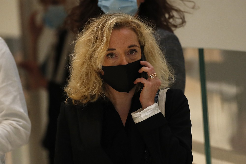Chloe Verlhac, widow of Charlie Hebdo cartoonist Tignous, arrives at the courtroom for the opening of the 2015 attacks trial, Wednesday, Sept. 2, 2020 in Paris. Thirteen men and a woman go on trial Wednesday over the 2015 attacks against a satirical newspaper and a kosher supermarket in Paris that marked the beginning of a wave of violence by the Islamic State group in Europe. Seventeen people and all three gunmen died during the three days of attacks in January 2015. (AP Photo/Francois Mori)