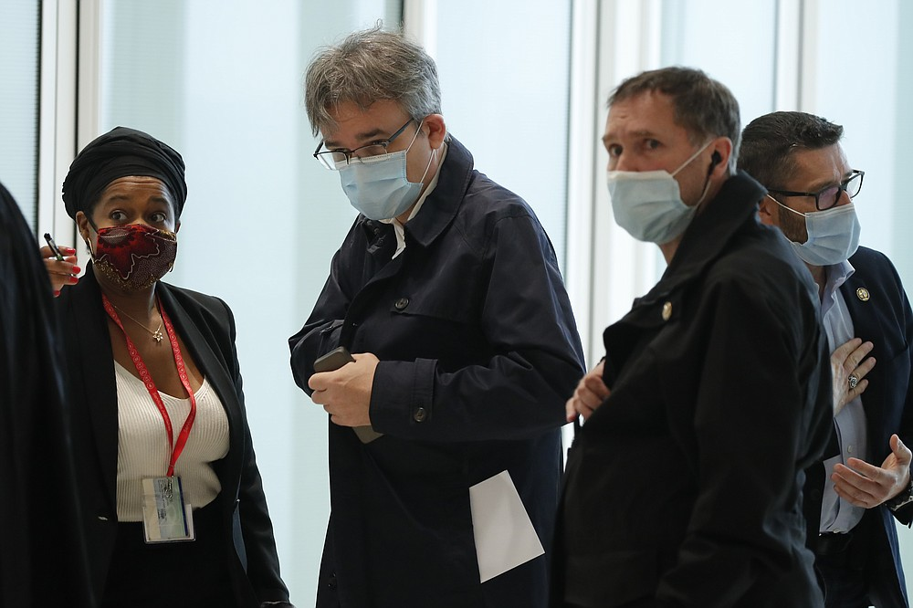 Satirical newspaper Charlie Hebdo's chief editor, Laurent Sourisseau, known as Riss, center, arrives at the courtroom for the opening of the 2015 attacks trial, Wednesday, Sept. 2, 2020 in Paris. Thirteen men and a woman go on trial Wednesday over the 2015 attacks against a satirical newspaper and a kosher supermarket in Paris that marked the beginning of a wave of violence by the Islamic State group in Europe. Seventeen people and all three gunmen died during the three days of attacks in January 2015. (AP Photo/Francois Mori)