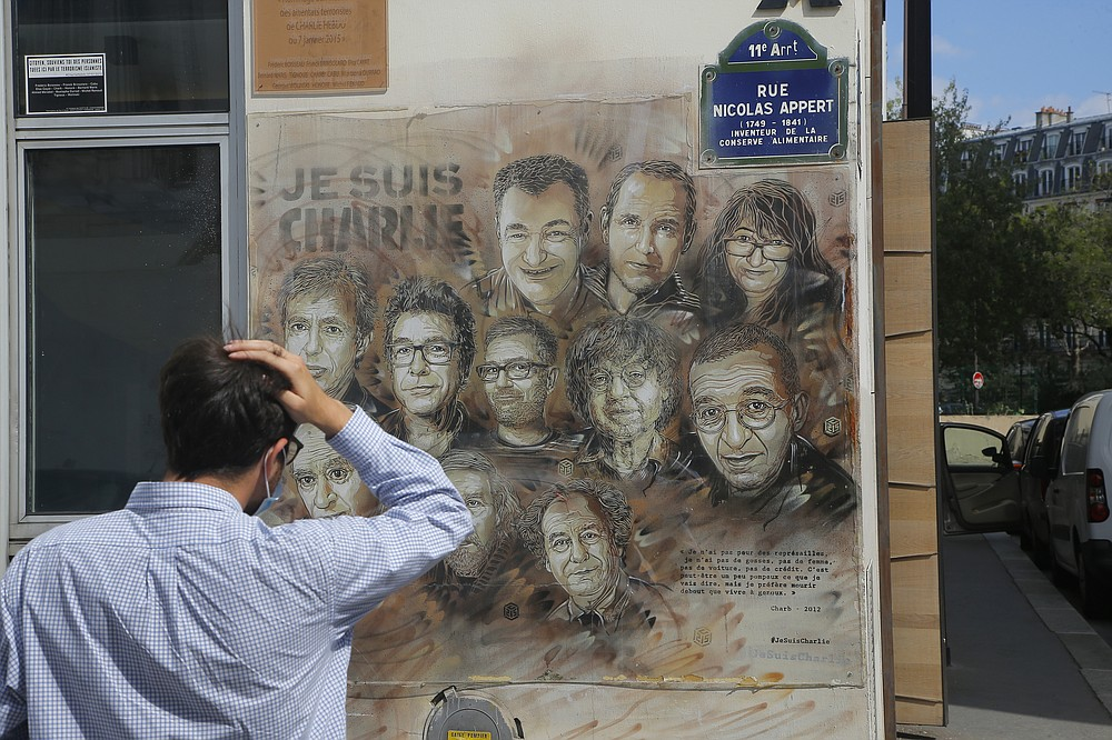 A man wearing a protective face mask as a precaution against the coronavirus looks on a painting by French street artist Christian Guemy, a.k.a. 'C215' in Paris Wednesday, Sept. 2, 2020, in tribute to the members of the satirical newspaper Charlie Hebdo attack by jihadist gunmen in January 2015. Thirteen men and a woman go on trial Wednesday over the 2015 attacks against a satirical newspaper and a kosher supermarket in Paris that marked the beginning of a wave of violence by the Islamic State group in Europe. Seventeen people and all three gunmen died during the three days of attacks in January 2015. (AP Photo/Michel Euler)