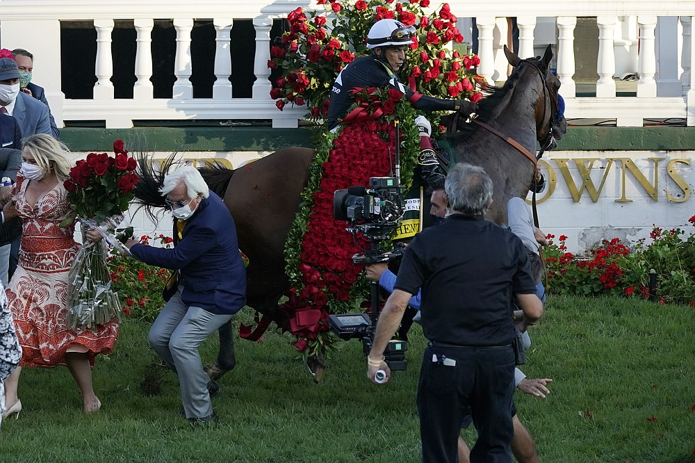 Trainer Bob Baffert is knocked to ground as Jockey John Velazquez try to control Authentic in the winners' circle after winning the 146th running of the Kentucky Derby at Churchill Downs, Saturday, Sept. 5, 2020, in Louisville, Ky. (AP Photo/Jeff Roberson)