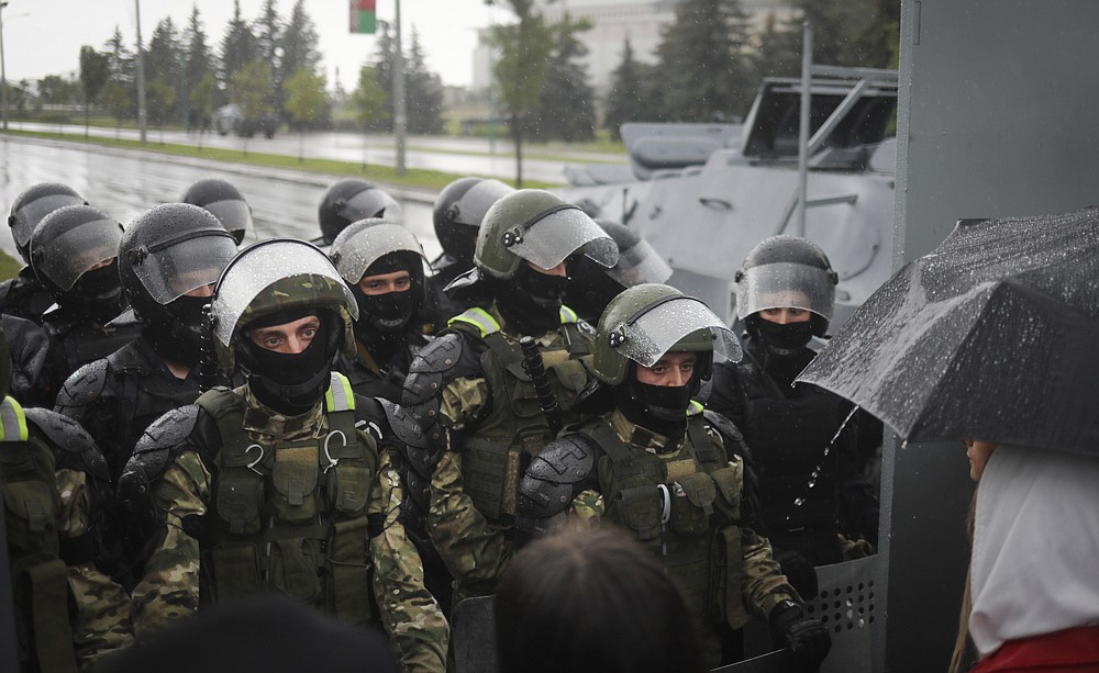 Riot police line block the road to stop Belarusian opposition supporters rally near the Palace of Independence in Minsk, Belarus, Sunday, Sept. 6, 2020. Sunday's demonstration marked the beginning of the fifth week of daily protests calling for Belarusian President Alexander Lukashenko's resignation in the wake of allegedly manipulated elections. (AP Photo/TUT.by)