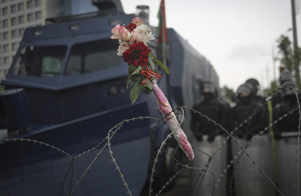 Flowers lie on the barbed wire separating Belarusian servicemen and Belarusian opposition supporters during a rally to protest the official presidential election results in Minsk, Belarus, Sunday, Sept. 6, 2020. Sunday's demonstration marked the beginning of the fifth week of daily protests calling for Belarusian President Alexander Lukashenko's resignation in the wake of allegedly manipulated elections. (AP Photo/TUT.by)