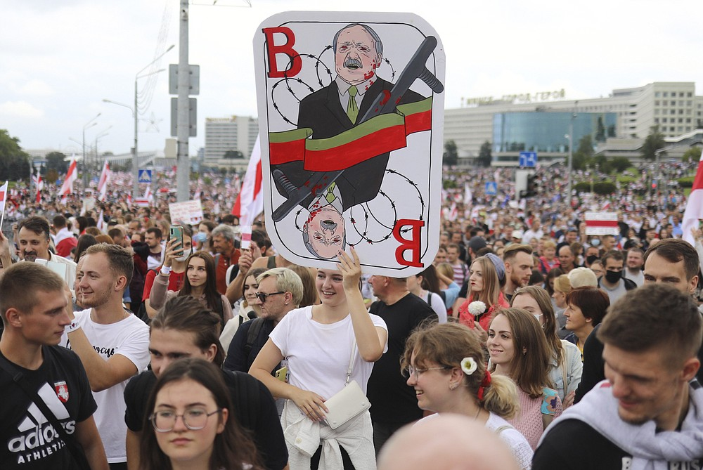 A woman holds a caricature of Belarus President Alexander Lukashenko during an opposition rally to protest the official presidential election results in Minsk, Belarus, Sunday, Sept. 6, 2020. Sunday's demonstration marked the beginning of the fifth week of daily protests calling for Belarusian President Alexander Lukashenko's resignation in the wake of allegedly manipulated elections. (AP Photo/TUT.by)