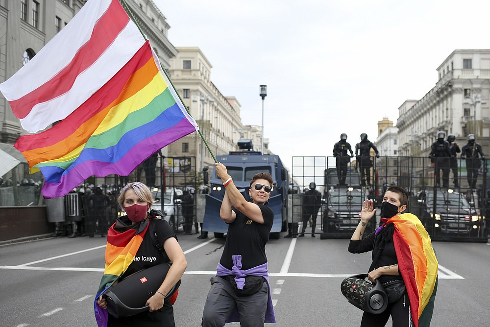 LGBT activists perform with rainbow flags and an old Belarusian national flag, in front of a police barricade blocking a street during an opposition rally to protest the official presidential election results in Minsk, Belarus, Sunday, Sept. 6, 2020. Sunday's demonstration marked the beginning of the fifth week of daily protests calling for Belarusian President Alexander Lukashenko's resignation in the wake of allegedly manipulated elections. (AP Photo/TUT.by)