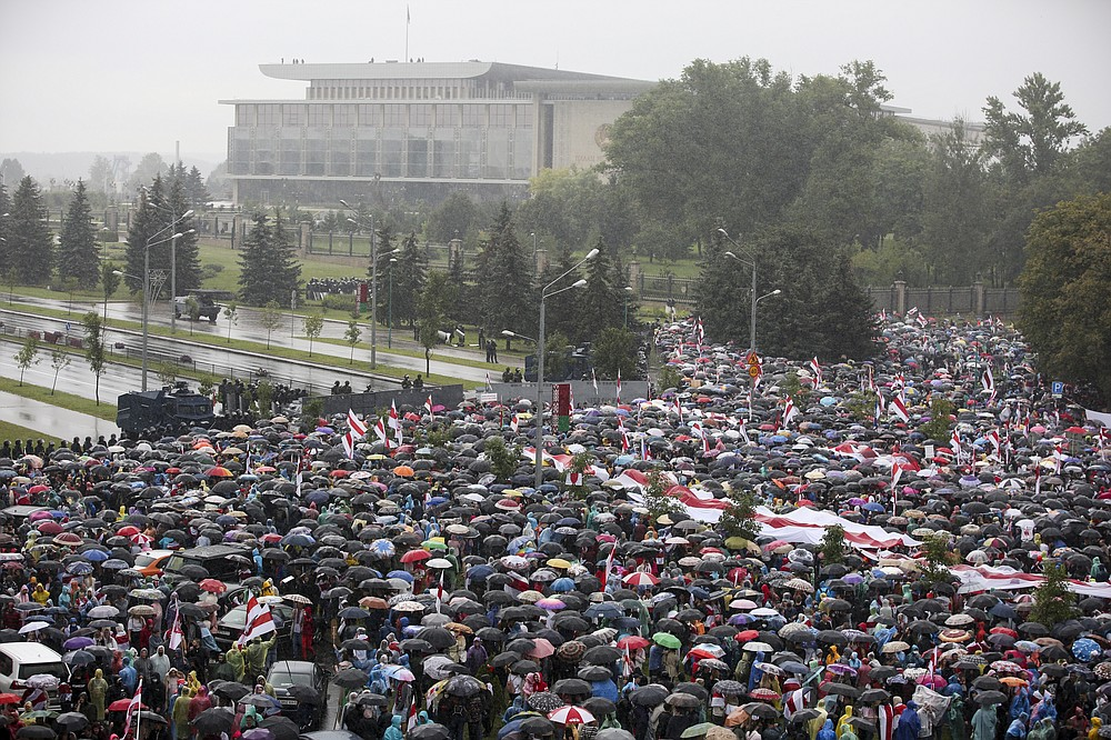Belarusian opposition supporters gather in front of police line toward the Independence Palace, residence of the President Alexander Lukashenko, in the background, in Minsk, Belarus, Sunday, Sept. 6, 2020. Sunday's demonstration marked the beginning of the fifth week of daily protests calling for Belarusian President Alexander Lukashenko's resignation in the wake of allegedly manipulated elections. (AP Photo/TUT.by)
