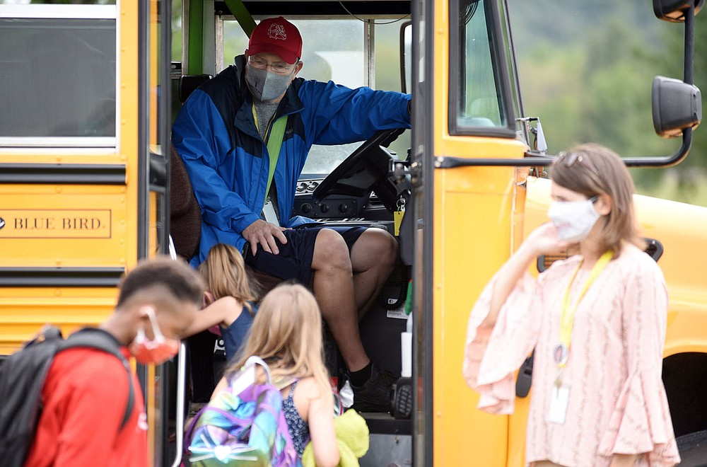 Rob Ariola, bus driver with the Springdale Public School District, greets students Tuesday, September 1, 2020, as they apply hand sanitizer while entering the bus for a ride home from Monitor Elementary School in Springdale. Check out nwaonline.com/200903Daily/ and nwadg.com/photos for a photo gallery. (NWA Democrat-Gazette/David Gottschalk)