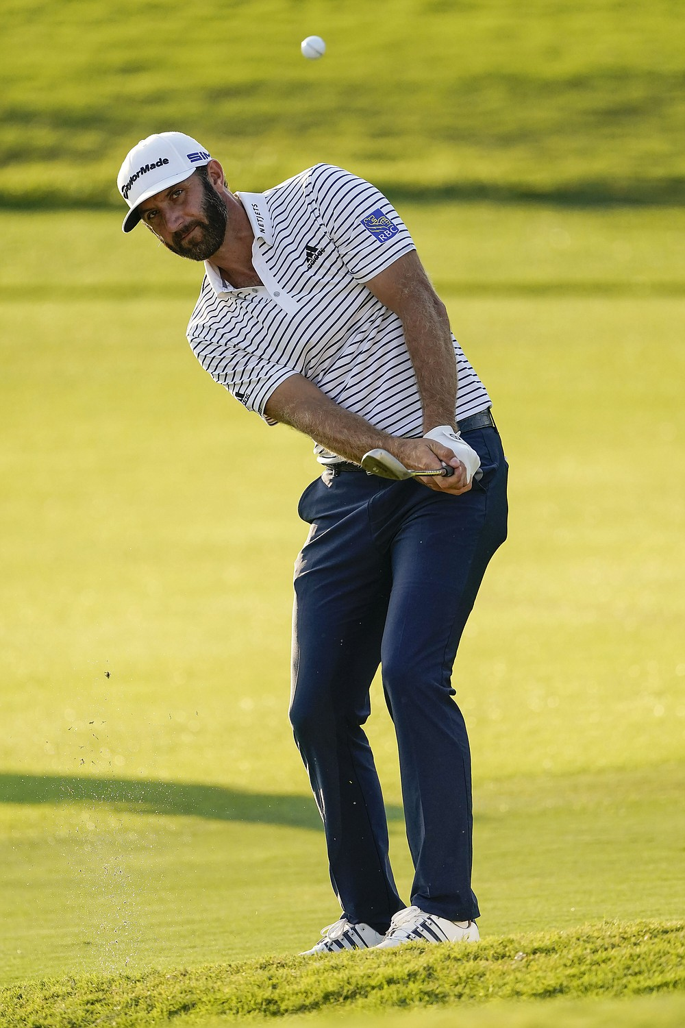 Dustin Johnson chips to the green on the 18th hole during the third round of the Tour Championship golf tournament at East Lake Golf Club in Atlanta, Sunday, Sept. 6, 2020. (AP Photo/John Bazemore)