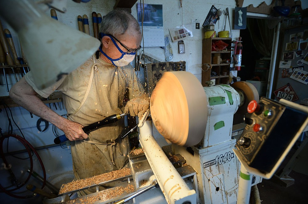 Woodworker Greg Thomas begins the process of turning a bowl from a piece of cherry Tuesday, Aug. 18, 2020, while working in his workshop at his home near Elkins. Visit nwaonline.com/200819Daily/ for today's photo gallery. (NWA Democrat-Gazette/Andy Shupe)