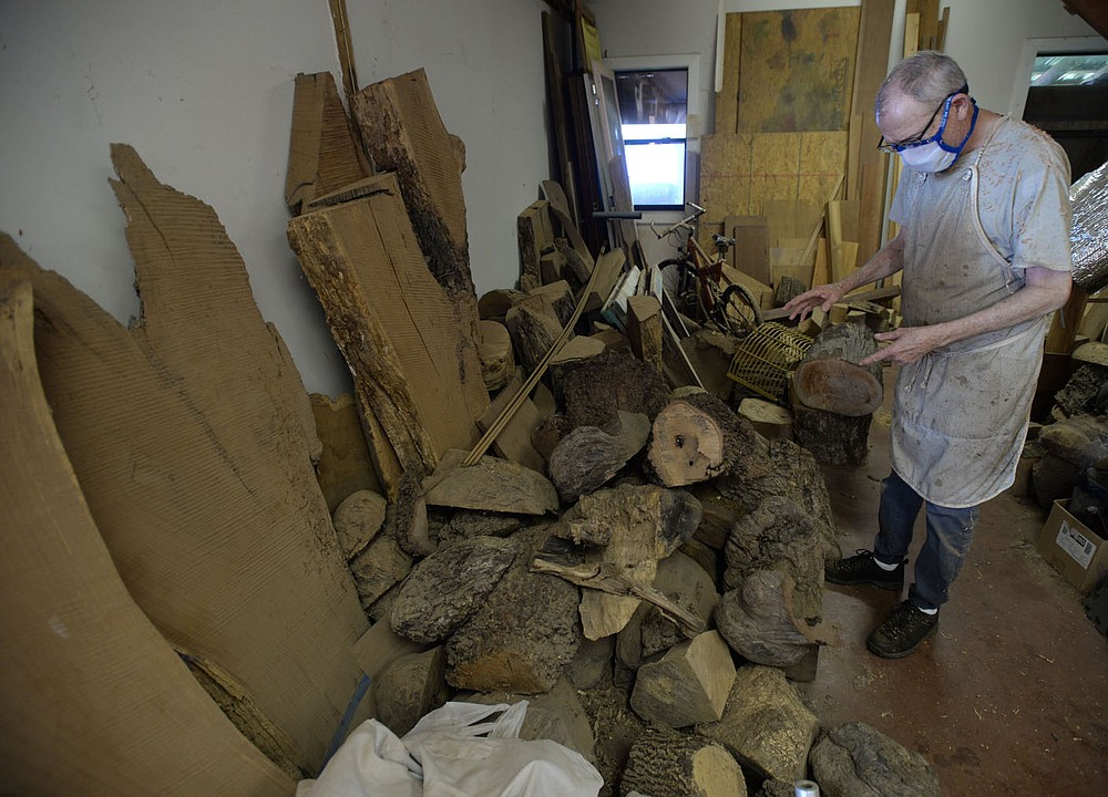 Woodworker Greg Thomas shows his collection of burls of several different species of tree Tuesday, Aug. 18, 2020, in his workshop at his home near Elkins. Visit nwaonline.com/200819Daily/ for today's photo gallery. (NWA Democrat-Gazette/Andy Shupe)