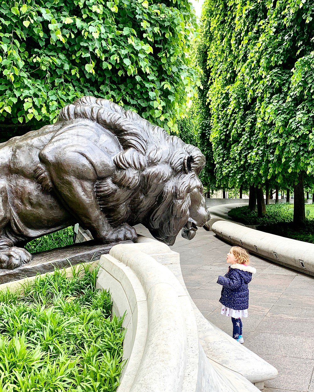 Adelynn Graff stares at one of the lion statues that are part of the National Law Enforcement Officers Memorial in Judiciary Square. (The Washington Post/Austin Graff)