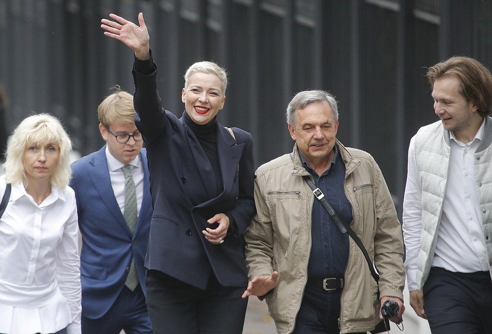 FILE - In this Aug. 27, 2020, file photo, Maria Kolesnikova, one of Belarus' opposition leaders, center left, and her father Alexander, center right, walk on the way to the Belarusian Investigative Committee in Minsk, Belarus. Kolesnikova, a professional flute player with no political experience, emerged as a key opposition activist in Belarus. She has appeared at protests of authoritarian President Alexander Lukashenko after he was kept in power by an Aug. 9 election that his critics say was rigged. (AP Photo/Dmitri Lovetsky, File)