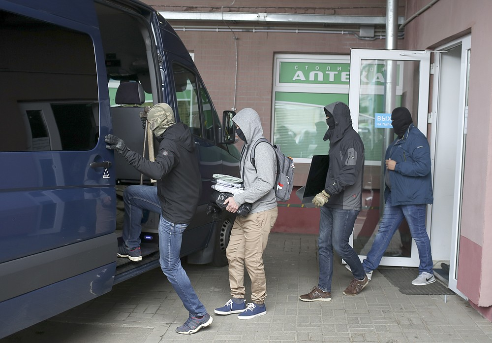 Authorities carry documents and computers out of the opposition Coordination Council office after a search raid in Minsk, Belarus, Wednesday Sept. 9, 2020. Belarusian authorities on Wednesday detained one of the last leading members of an opposition council who remained free, moving methodically to end a month of protests against authoritarian President Alexander Lukashenko. (AP Photo/TUT.by)