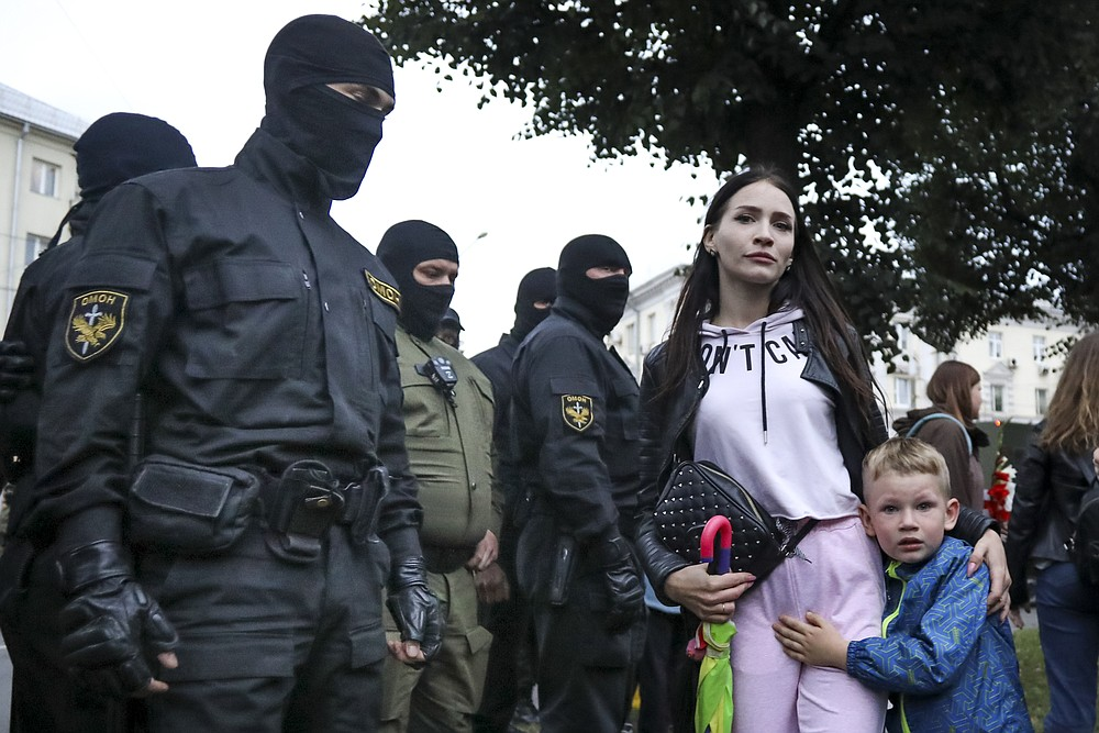 A woman with her child react as police officers detain protesters during a rally in support of Maria Kolesnikova, a member of the Coordination Council created by the opposition to facilitate talks with Lukashenko on a transition of power, was detained Monday in the capital of Minsk with two other council members, in Minsk, Belarus, Tuesday, Sept. 8, 2020. A leading opposition activist in Belarus is being held on the border with Ukraine after she resisted attempts by authorities to deport her from the country as part of a clampdown on protests against authoritarian President Alexander Lukashenko. (AP Photo)