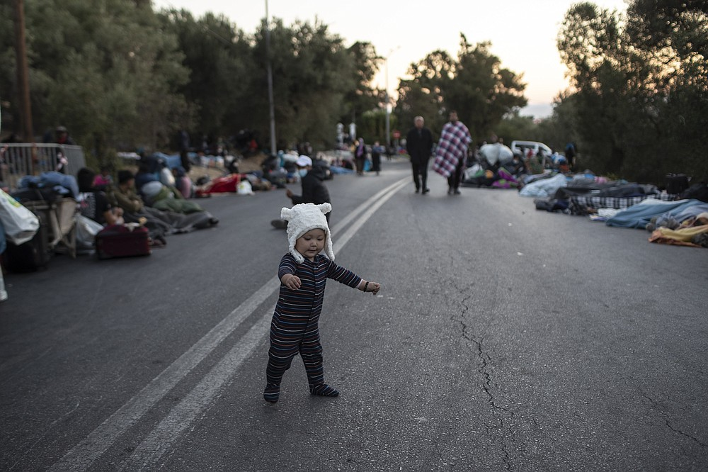 A boy tries to stand as migrants sleep on the road near the Moria refugee camp on the northeastern island of Lesbos, Greece, Thursday, Sept. 10, 2020. A second fire in Greece's notoriously overcrowded Moria refugee camp destroyed nearly everything that had been spared in the original blaze, Greece's migration ministry said Thursday, leaving thousands more people in need of emergency housing. (AP Photo/Petros Giannakouris)