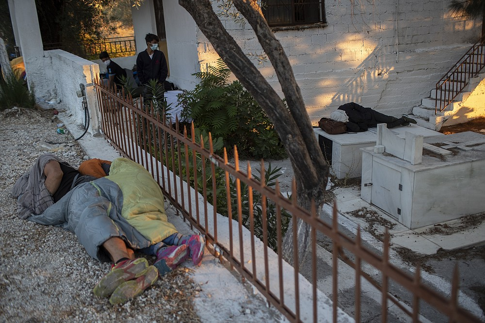 Migrants sleep at a cemetery near the Moria refugee camp on the northeastern island of Lesbos, Greece, Thursday, Sept. 10, 2020. A second fire in Greece's notoriously overcrowded Moria refugee camp destroyed nearly everything that had been spared in the original blaze, Greece's migration ministry said Thursday, leaving thousands more people in need of emergency housing. (AP Photo/Petros Giannakouris)