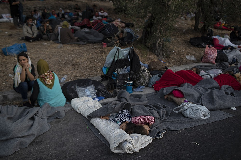 Migrants sleep on the road near the Moria refugee camp on the northeastern island of Lesbos, Greece, Thursday, Sept. 10, 2020. A second fire in Greece's notoriously overcrowded Moria refugee camp destroyed nearly everything that had been spared in the original blaze, Greece's migration ministry said Thursday, leaving thousands more people in need of emergency housing. (AP Photo/Petros Giannakouris)