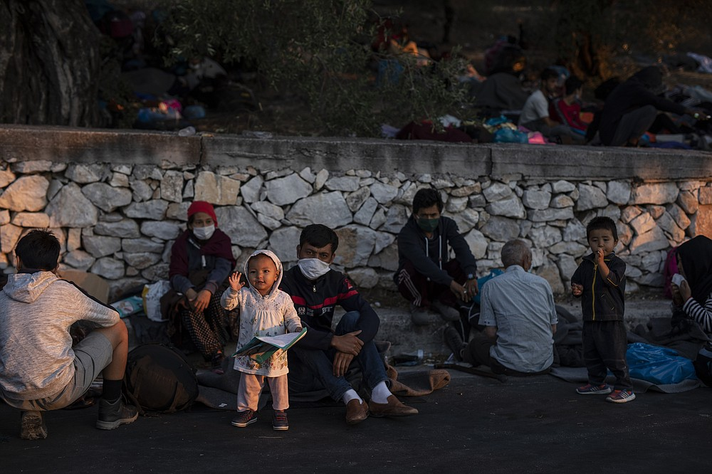 Migrants gather on the road near the Moria refugee camp on the northeastern island of Lesbos, Greece, Thursday, Sept. 10, 2020. A second fire in Greece's notoriously overcrowded Moria refugee camp destroyed nearly everything that had been spared in the original blaze, Greece's migration ministry said Thursday, leaving thousands more people in need of emergency housing. (AP Photo/Petros Giannakouris)