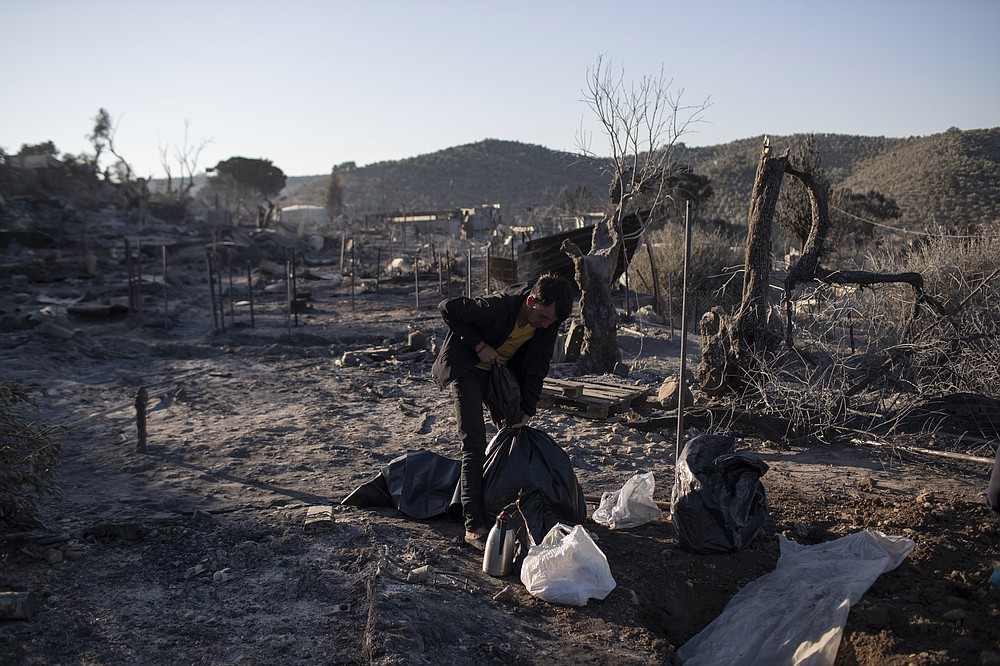 A migrant is tighten a plastic bag in the burned Moria refugee camp on the northeastern island of Lesbos, Greece, Thursday, Sept. 10, 2020. A second fire in Greece's notoriously overcrowded Moria refugee camp destroyed nearly everything that had been spared in the original blaze, Greece's migration ministry said Thursday, leaving thousands more people in need of emergency housing. (AP Photo/Petros Giannakouris)