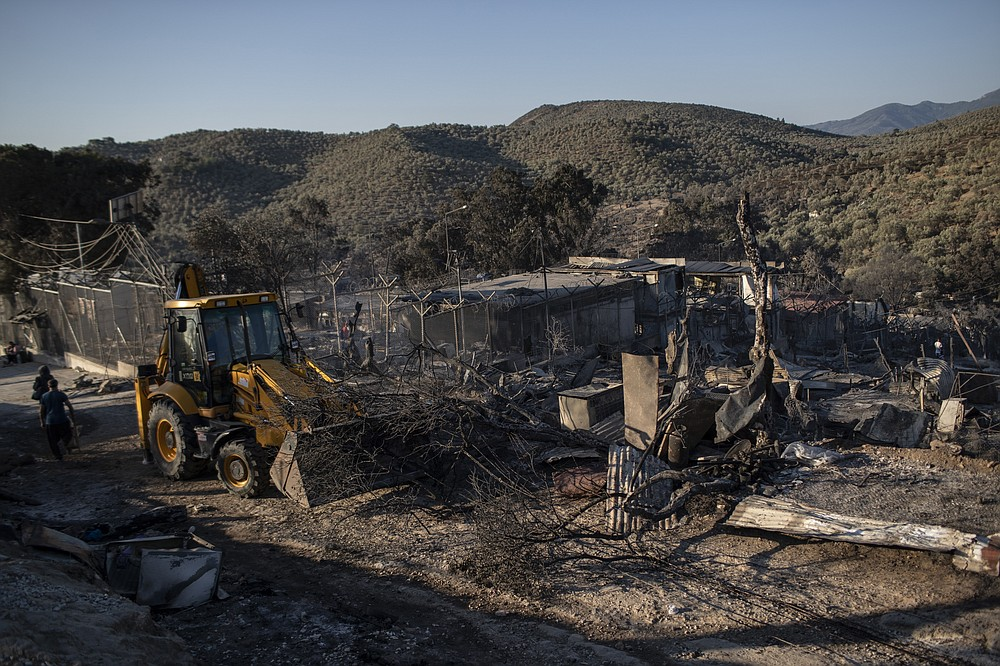 A bulldozer removes the debris from the burned Moria refugee camp on the northeastern island of Lesbos, Greece, Thursday, Sept. 10, 2020. A second fire in Greece's notoriously overcrowded Moria refugee camp destroyed nearly everything that had been spared in the original blaze, Greece's migration ministry said Thursday, leaving thousands more people in need of emergency housing. (AP Photo/Petros Giannakouris)