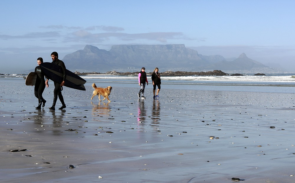 People walk on a beach, with Table Mountain in the background, in Cape Town, South Africa, Wednesday Aug. 19, 2020. Africa's tourism sector is struggling to cope with the drop in international travel caused by the COVID-19 pandemic. The World Travel and Tourism Council estimates the drop in travel caused by the COVID-19 pandemic will see Africa lose between $53 billion and $120 billion in contributions to its GDP in 2020. ( AP Photo/Nardus Engelbrecht)
