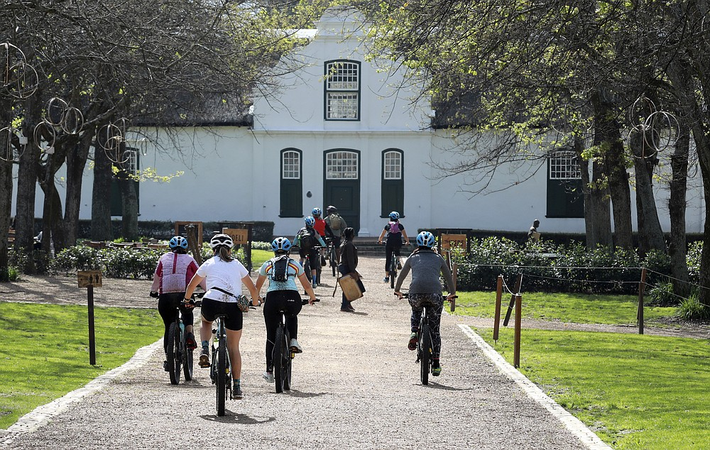 Local tourists are seen during an adventure e-bike tour, run by tour operator Raino Bolz, on the Boschendal Estate near, Cape Town South Africa, Friday, Sept. 4, 2020. Africa's tourism sector is struggling to cope with the drop in international travel caused by the COVID-19 pandemic. The World Travel and Tourism Council estimates the drop in travel caused by the COVID-19 pandemic will see Africa lose between $53 billion and $120 billion in contributions to its GDP in 2020. (AP Photo/Nardus Engelbrecht)