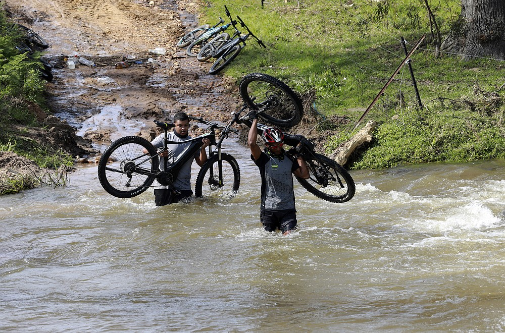 Tour guides, Colin de Wet and Severiano Tamboer, who work for tour operator Raino Bolz, cross a river during an adventure e-bike tour, between Stellenboschon and the Boschendal Estate near, Cape Town South Africa, Friday Sept. 4, 2020. Africa's tourism sector is struggling to cope with the drop in international travel caused by the COVID-19 pandemic. The World Travel and Tourism Council estimates the drop in travel caused by the COVID-19 pandemic will see Africa lose between $53 billion and $120 billion in contributions to its GDP in 2020. (AP Photo/Nardus Engelbrecht)