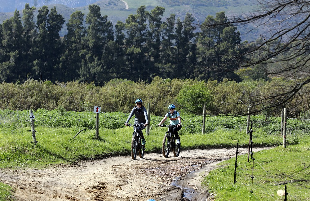 Local tourists are seen during an adventure e-bike tour, run by tour operator Raino Bolz, on the Boschendal Estate near, Cape Town, South Africa, Friday Sept. 4, 2020. Africa's tourism sector is struggling to cope with the drop in international travel caused by the COVID-19 pandemic. The World Travel and Tourism Council estimates the drop in travel caused by the COVID-19 pandemic will see Africa lose between $53 billion and $120 billion in contributions to its GDP in 2020. ( AP Photo/Nardus Engelbrecht)