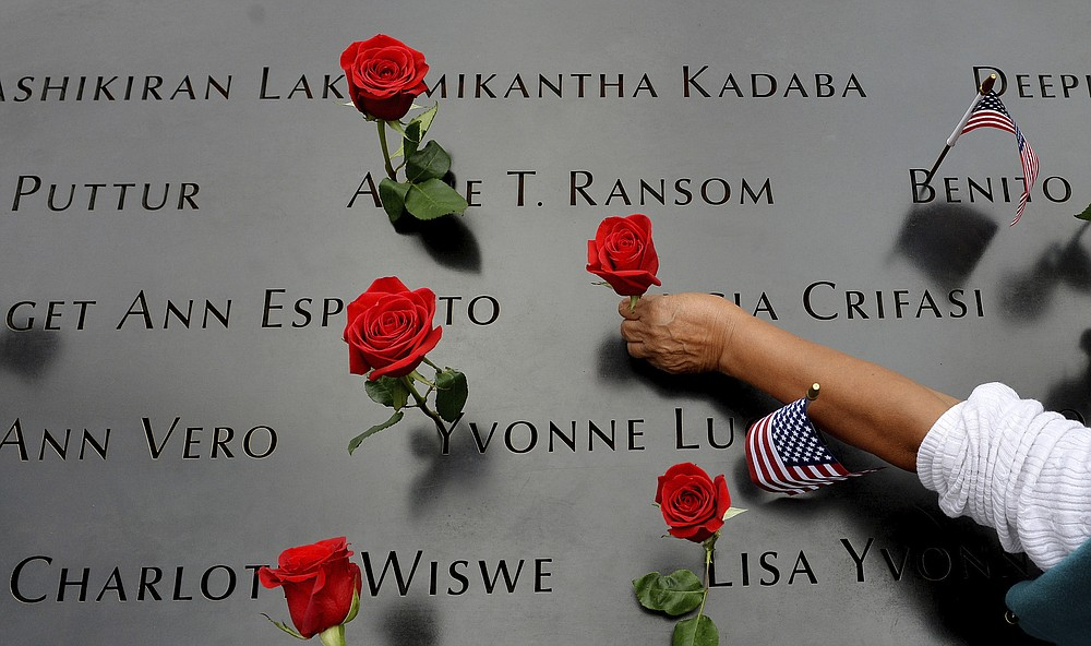 FILE - In this Sept. 11, 2014, file photo, a woman places flowers in the inscribed names along the edge of the North Pool during memorial observances on the 13th anniversary of the Sept. 11, 2001 terror attacks on the World Trade Center in New York. The coronavirus pandemic has reshaped how the U.S. is observing the anniversary of 9/11. The terror attacks' 19th anniversary will be marked Friday, Sept. 11, 2020, by dueling ceremonies at the Sept. 11 memorial plaza and a corner nearby in New York. (AP Photo/Justin Lane, Pool, File)