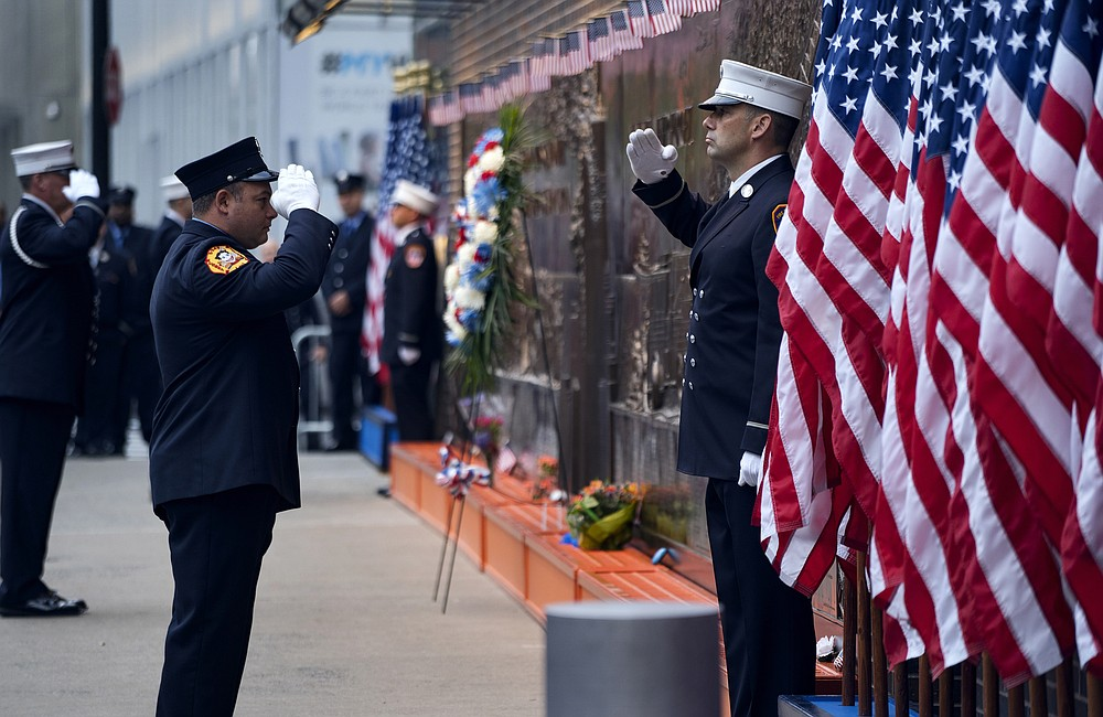 FILE - In this Sept. 11, 2018, file photo, New York City firefighters salute in front of a memorial on the side of a firehouse adjacent to One World Trade Center and the 9/11 Memorial site during ceremonies on the anniversary of 9/11 terrorist attacks in New York. Because of the coronavirus, the Fire Department has urged members to stay away from any of the 2020 observances of the 2001 terror strike that killed nearly the 3,000 people, among them almost 350 firefighters. (AP Photo/Craig Ruttle, File)