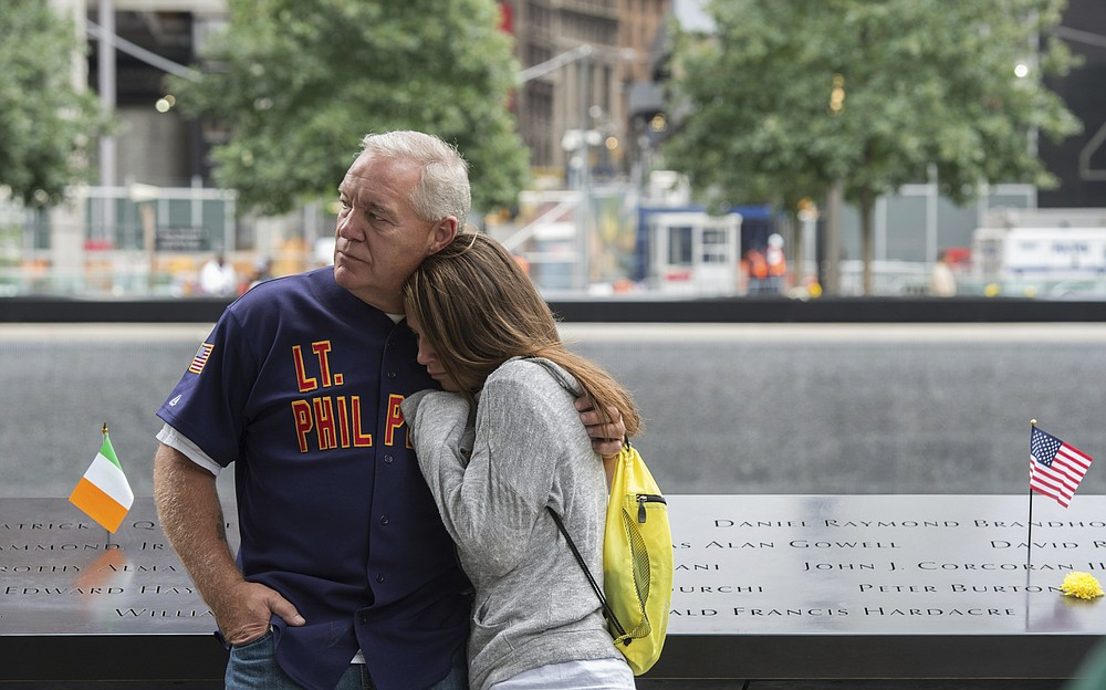 FILE - In this Sept. 11, 2015, file photo, victims' family members look on during a ceremony at the World Trade Center site in New York. The coronavirus pandemic has reshaped how the U.S. is observing the anniversary of 9/11. The terror attacks' 19th anniversary will be marked Friday, Sept. 11, 2020, by dueling ceremonies at the Sept. 11 memorial plaza and a corner nearby in New York. (AP Photo/Bryan R. Smith, File)