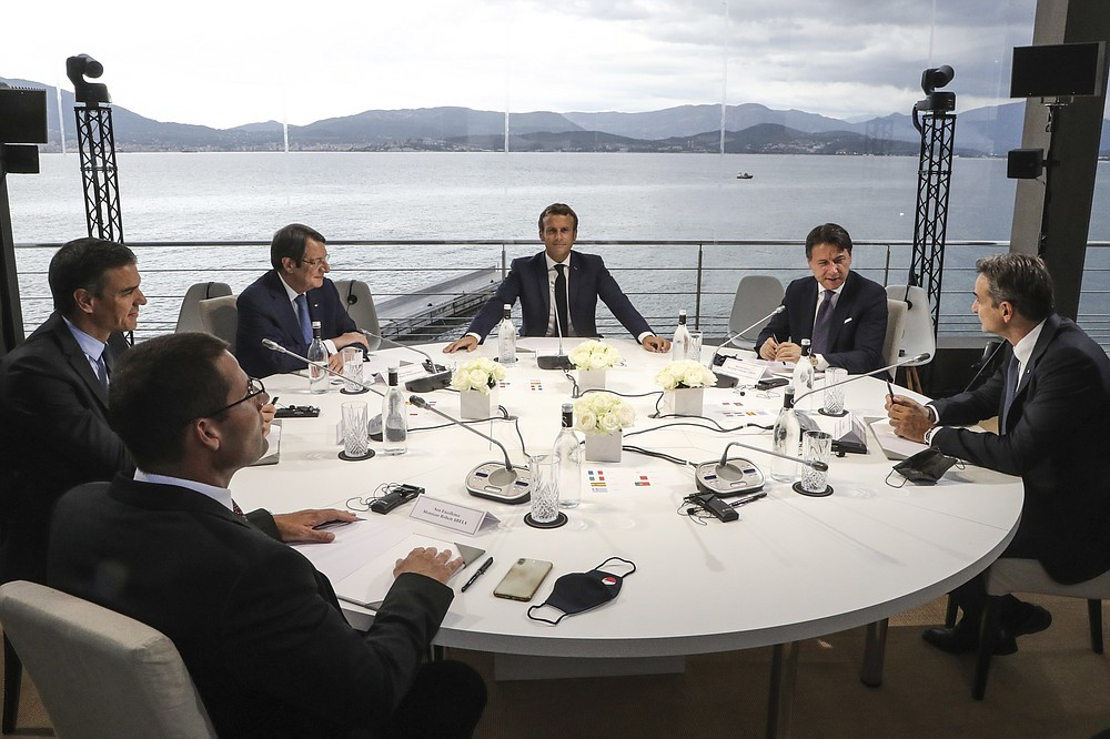 Clockwise from left, Malta's Prime Minister Robert Abela, Spain's Prime Minister Pedro Sanchez, Cyprus President Nikos Anastasiadis, France's President Emmanuel Macron, Italy's Prime Minister Giuseppe Conte and Greek Prime Minister Kyriakos Mitsotakis meet during an emergency summit in Porticcio, Corsica island, Thursday Sept.10, 2020. Leaders of EU countries on the Mediterranean Sea are holding an emergency summit in Corsica on Thursday amid fears of open conflict with Turkey stemming from mounting tensions over oil and gas drilling. (Ludovic Marin/Pool Photo via AP)