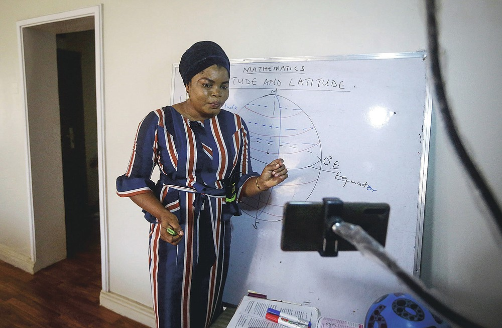 Mathematics teacher Basirat Olamide Ajayi, 36, teaches longitude and latitude online via her mobile phone from her house in Lagos, Nigeria Saturday, Aug. 15, 2020. The teacher from a Lagos public school is helping students across the country, and internationally, learn math virtually during coronavirus restrictions that have prevented most children from returning to class in Nigeria. (AP Photo/Sunday Alamba)