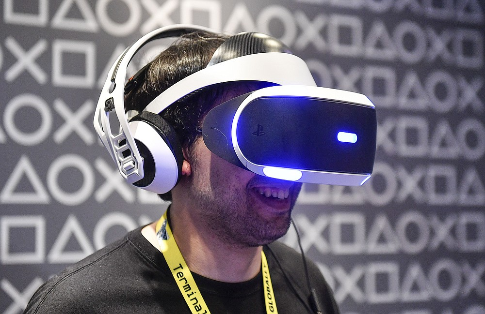 FILE - In this Aug. 20, 2019 file photo, a man testing a Sony PlayStation Virtual Reality headset at the Gamescom in Cologne, Germany. Streaming high-definition video and games can result in significant greenhouse gas emissions, depending on the technology used, according to a German government-backed study released Thursday. (AP Photo/Martin Meissner)