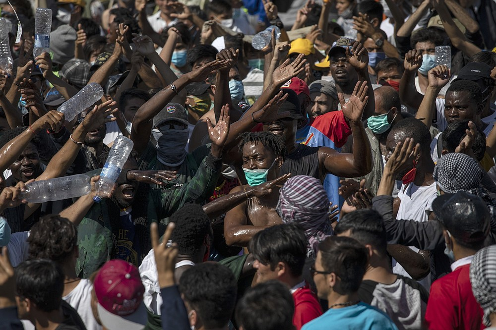 Migrants take part in a rally near Mytilene town, on the northeastern island of Lesbos, Greece, Friday, Sept. 11, 2020. Thousands of protesting refugees and migrants left homeless on the Greek island of Lesbos after fires destroyed the notoriously overcrowded Moria camp have gathered on a road leading to the island's main town, demanding to be allowed to leave. (AP Photo/Petros Giannakouris)
