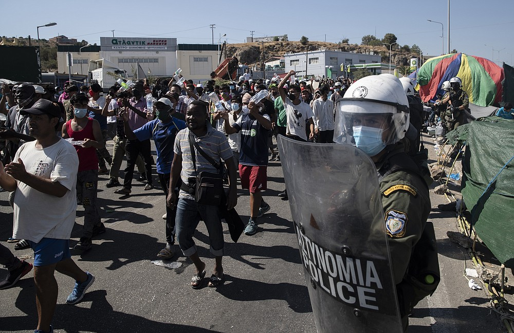 Migrants take part in a rally as riot police block the road near Mytilene town, on the northeastern island of Lesbos, Greece, Friday, Sept. 11, 2020. Thousands of protesting refugees and migrants left homeless on the Greek island of Lesbos after fires destroyed the notoriously overcrowded Moria camp have gathered on a road leading to the island's main town, demanding to be allowed to leave. (AP Photo/Petros Giannakouris)