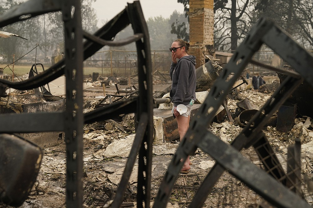 """Desiree Pierce reacts as she visits her home destroyed by the Almeda Fire, Friday, Sept. 11, 2020, in Talent, Ore. """"I just needed to see it, to get some closure,"""" said Pierce.  (AP Photo/John Locher)"""