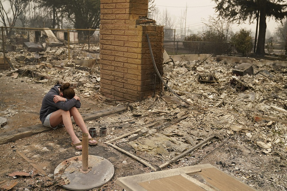 """Desiree Pierce cries as she visits her home destroyed by the Almeda Fire, Friday, Sept. 11, 2020, in Talent, Ore. """"I just needed to see it, to get some closure,"""" said Pierce. (AP Photo/John Locher)"""