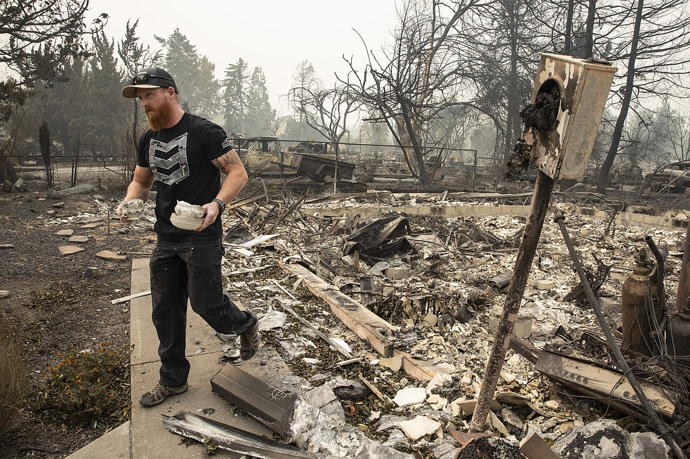 Derek Trenton from Talent, Ore. salvages some items at his parents home as wildfires devastate the region, Friday, Sept. 11, 2020 in Talent, Ore. (AP Photo/Paula Bronstein)