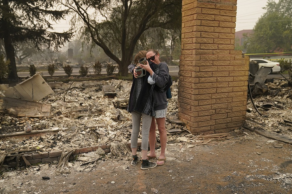 Desiree Pierce, right, hugs her step daughter Leah Johnson as they visit their home destroyed by the Almeda Fire, Friday, Sept. 11, 2020, in Talent, Ore.  (AP Photo/John Locher)