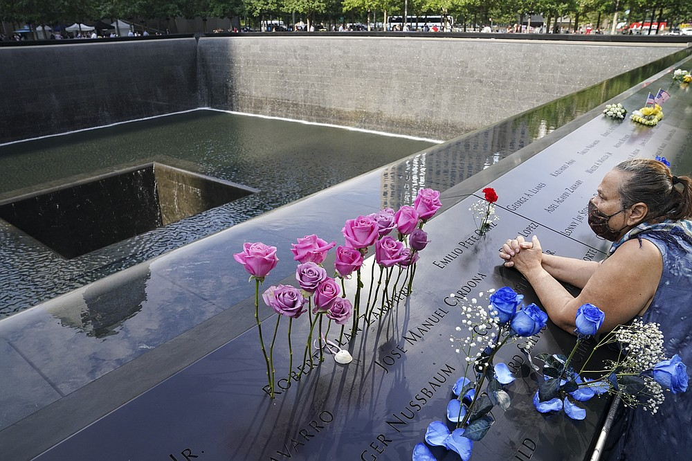 A mourner prays over the name cut-out of the deceased Emilio Pete Ortiz at the National September 11 Memorial and Museum, Friday, Sept. 11, 2020, in New York. Americans will commemorate 9/11 with tributes that have been altered by coronavirus precautions and woven into the presidential campaign. (AP Photo/John Minchillo)